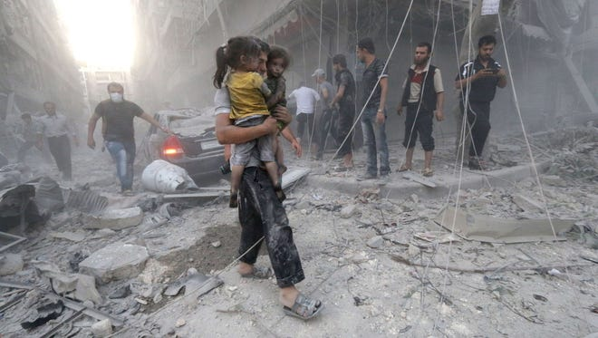 A Syrian man carries two girls covered with dust after an airstrike July 9 in the northern city of Aleppo.