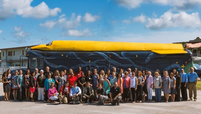 Members of the Moonshot Community Action Network pose with the Reading Rocket.