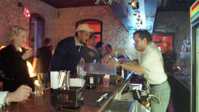 Co-owner Marcos Canchola tends bar on the opening night of MugShots in 2002.