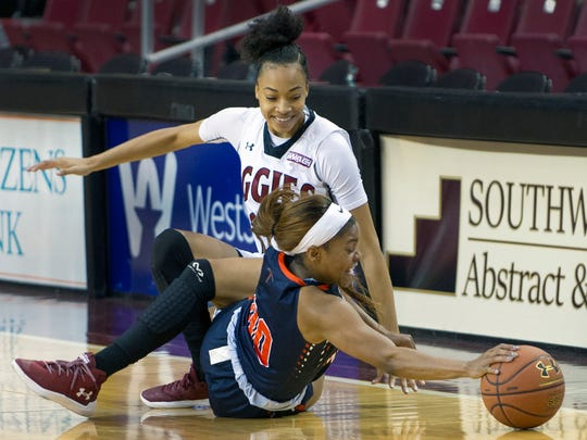 New Mexico State's Monique Mills gets tangled up with UTEP's Jordan Jenkins going for the loose ball Sunday afternoon at the Pan American Center.