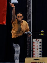 Makayla Murray stretches an arm and lifts a leg for balance while competing Saturday night in a cornhole tournament at the Abilene Convention Center.
