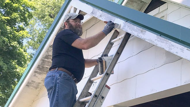 Andy Gorges, a volunteer with Corning Veterans Engaged to Support (C-VETS), applies paint to the Disabled American Veterans headquarters in Elmira Heights on Thursday as part of the United Way Day of Action.