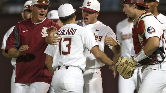 FSU's Drew Parrish, center, who pitched eight scoreless innings, celebrates with Jonah Scolaro (13) who pitched his way out of a bases loased jam in the top of the ninth as the Seminoles defeat Miami 2-0 on Friday at Dick Howser Stadium.