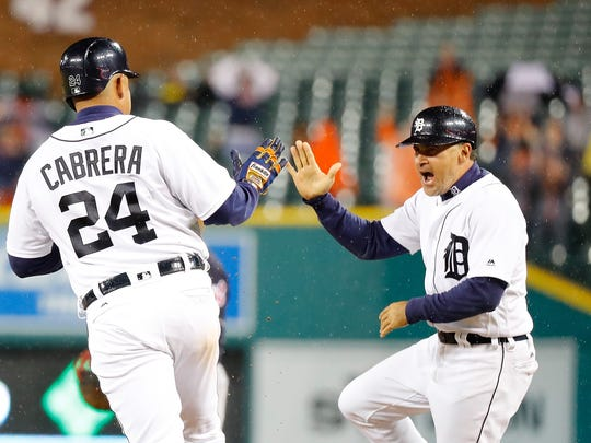 Tigers' Miguel Cabrera hits a three-run home run and celebrates with first base coach Omar Vizquel during the fifth inning against the Cleveland Indians on September 28, 2016 at Comerica Park in Detroit.