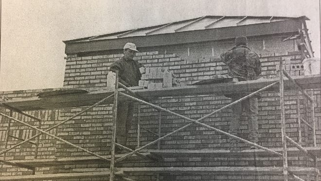 Louie Courtney, left, and Bryan Hughes put the final bricks on the outside of the new location of Subway in January 2000.