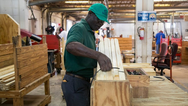 Lance Robinson works packaging survey stakes in the wood shop at LARC in Fort Myers.