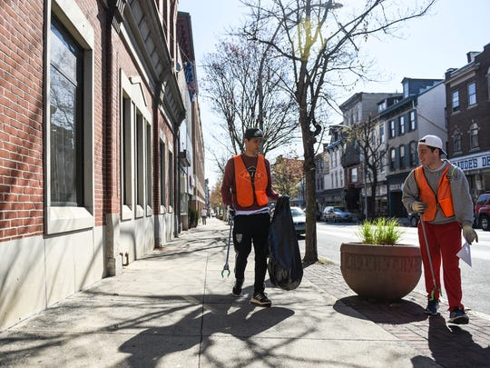Annville-Cleona exchange students from Spain, Javier Gonzalez Sanchez (left), a senior, and Santiago Paris Gimeno, a junior, pick up garbage along Cumberland Street as 17 volunteers headed into Lebanon's business improvement district to pick up garbage on Saturday, April 16, 2016. The volunteers from various organizations like Lebanon Valley College, Boy Scout Troop 415 and Annville-Cleona High School picked up 21 bags of garbage weighing 189.1 pounds.