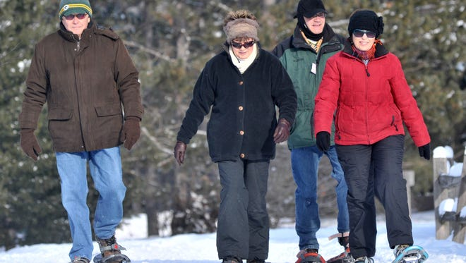 A group of people snowshoe at Nine Mile County Forest Recreation Area in Rib Mountain in 2012. On Dec. 26, 2015, Monk Botanical Gardens will hold its first winter snowshoe walk of the season.