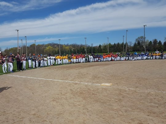 Plymouth-Canton Little League teams line up along the edge of the infield at McClumpha Park.