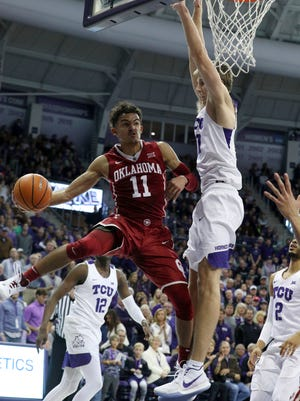 Oklahoma guard Trae Young (11) passes the ball around TCU forward Vladimir Brodziansky (10) during the first half of an NCAA college basketball game.