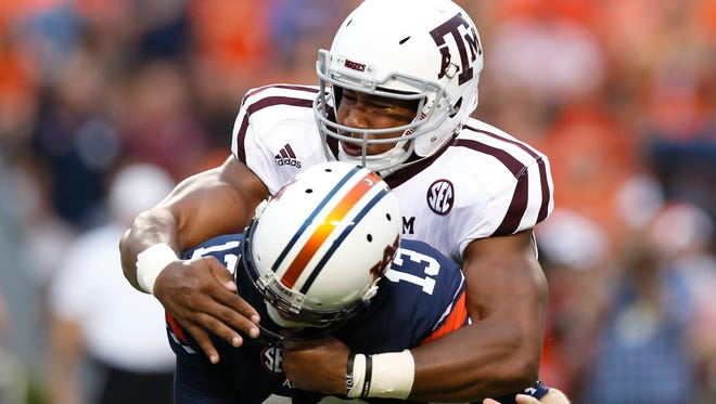 FILE - In  this Sept. 17, 2016, file photo, Texas A&M defensive lineman Myles Garrett, top, sacks Auburn quarterback Sean White in the first half of an NCAA college football game, Saturday, Sept. 17, 2016, in Auburn, Ala. Defense. That's going to be the area of concentration in this draft, in the first round and through much of the proceedings in Philadelphia. (AP Photo/Brynn Anderson, File)
