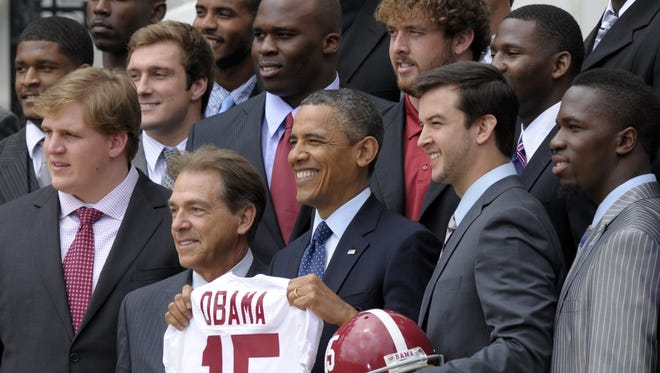 President Barack Obama holds up the Alabama Crimson Tide football jersey that he was presented after welcoming the BCS National Champion University of Alabama Crimson Tide football team to the White House to honor their 15th championship and their 2012-2013 season, Monday, April 15, 2013, on the South Lawn of the White House in Washington. Obama is flanked by head football coach Nick Saban, left, and quarterback A.J. McCarron, right. (AP Photo/Susan Walsh)