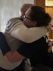 Michael Weidert, a Fox Valley Technical College adjunct fire instructor, hugs volunteer firefighter Alexis Rosker at her home in Kimberly, where she is recovering from injuries suffered in a fall from a ladder during a training exercise.