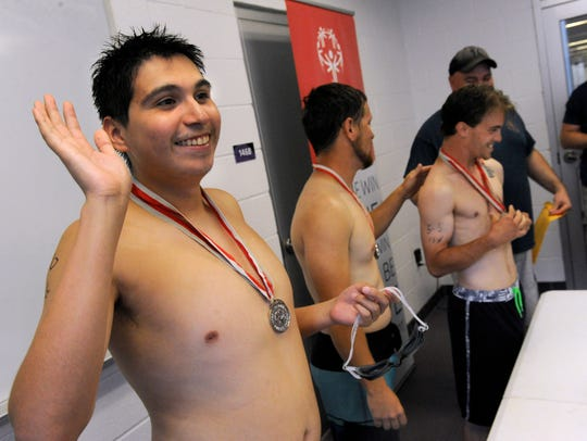 Mark Pena waves after being awarded a medal after Saturday's