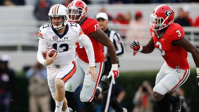 Auburn quarterback Sean White (13) scrambles as Georgia linebacker Davin Bellamy (17) and linebacker Roquan Smith (3) give chase in he first half of an NCAA college football game Saturday, Nov. 12, 2016, in Athens, Ga.