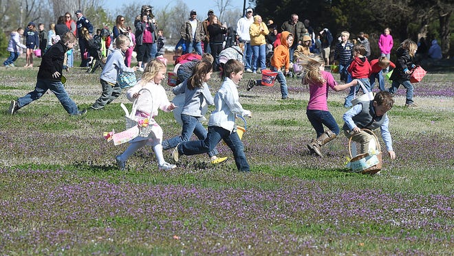 A gaggle of children run through a field Saturday at Cooper Park during the 20th Annual Junior Auxiliary Easter Egg Hunt. Hundreds of parents and children enjoyed sunny skies as they hunted eggs.