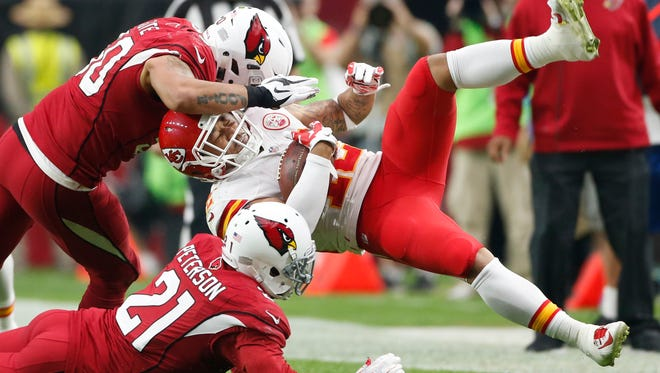 Kansas City Chiefs receiver Albert Wilson is tackled by Arizona Cardinals linebacker Larry Foote and cornerback Patrick Peterson (21) in the first quarter at University of Phoenix Stadium in Glendale on Dec. 7, 2014.