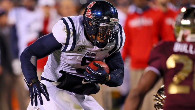 Ole Miss defensive end Robert Nkemdiche advances the ball as a running back during the game against Mississippi State at Davis Wade Stadium.