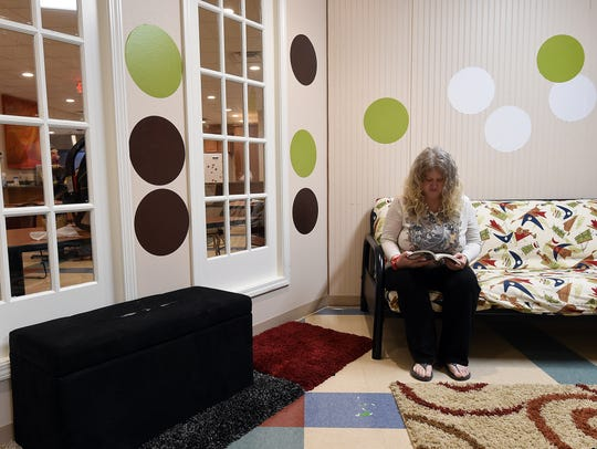 A client at Serenity spends time reading in this file photo. The ongoing government shutdown is endangering the future Supplemental Nutrition Assistance Program (SNAP) benefits, which are pooled by clients to provide food for all residents of the shelter.