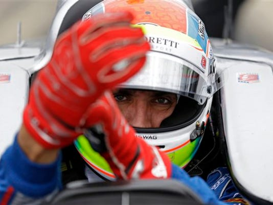 FILE - This is a May 14, 2015, file photo showing Justin Wilson, of England, putting on his gloves as he prepares to drive during practice for the Indianapolis 500 auto race at Indianapolis Motor Speedway in Indianapolis. The British driver was in a coma in critical condition after sustaining a head injury when he was hit by a large piece of debris that broke off another car in the crash-filled race at Pocono Raceway on Sunday, Aug. 23, 2015.