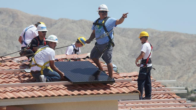 Students from Desert Hot Springs High School's Renewable Energy Academy of Learning and other volunteers install a solar panel on a Desert Hot Springs home on April 9, 2015.