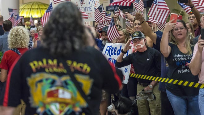 An enthusiastic crowd greets veterans arriving on the Southeast Florida Honor Flight at Palm Beach International Airport in West Palm Beach Saturday evening, May 11, 2019.  The flight included veterans of World War II, the Korean War and the Vietnam War. The Stuart-based organization has four flights per year that transport local war veterans to Washington, DC to visit the memorials built to honor them.