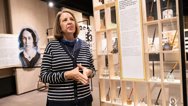 """Kansas Museum of History director Mary Madden pauses while talking Friday about Kansas and its roots as a leader in the suffragist movement during a tour of the suffrage exhibit """"Upward to Equality"""" at the museum. Over Madden's shoulder is a portrait of Kansan and suffragist Clarina Nichols."""
