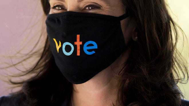 """FILE - In this Oct. 7, 2020, file photo, Michigan Gov. Gretchen Whitmer wears a mask with the word """"vote"""" displayed on the front in Kalamazoo, Mich. Michigan's Republican-led Legislature on Wednesday, Oct. 14, 2020, voted to keep intact longer-lasting unemployment benefits and other coronavirus-related orders issued by Democratic Gov. Gretchen Whitmer, while also striking a deal on liability protections for businesses."""
