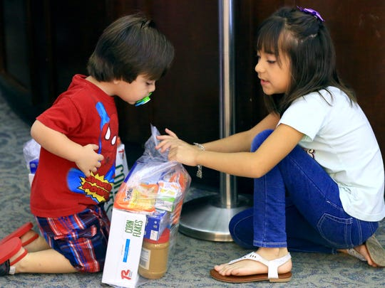 Johnny Cantu and his sister Sophia Cantu look through bags with food that were given by the Corpus Christi Food Bank on Friday, June 30, 2017, at the Keach Family Library in Robstown.