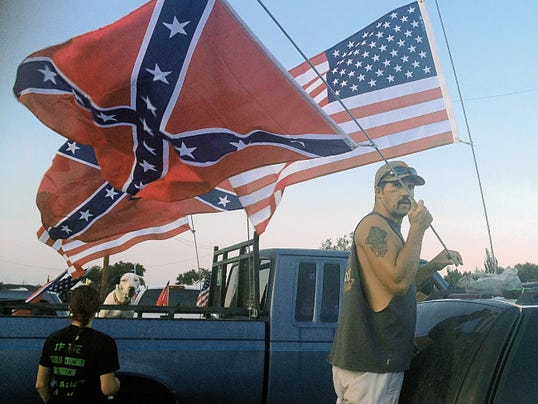 One of the participants in the Friday evening Confederate flag cruise raises both the U.S. and Confederate flags to display during the event.