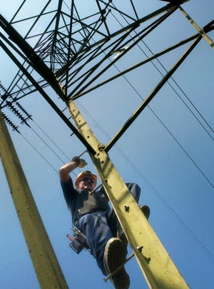 A Central Hudson Gas & Electric Corp. lineman and working foreman climbs a lattice tower on transmission line E, servicing central and eastern Dutchess County in Stanford.