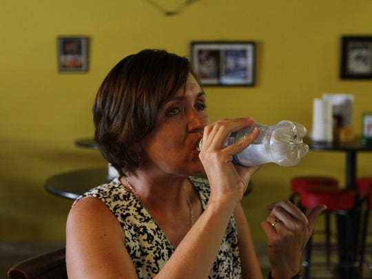 Anne Reed chugs water as tears well up after eating a Viper wing at Wingnuts in Cape Coral