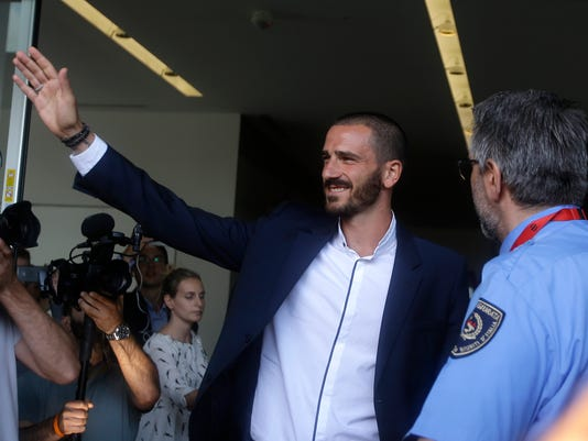 FILE - In this Friday, July 14, 2017 file photo, Italy defender Leonardo Bonucci waves to fans as he walks off AC Milan's headquarters, in Milan, Italy. Nothing is impossible. That's AC Milan's new unofficial slogan following Leonardo Bonucci's surprise transfer from defending six-time Serie A champion Juventus. (AP Photo/Luca Bruno, file)