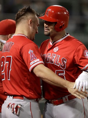 Los Angeles Angels' Albert Pujols, right, embraces Mike Trout after hitting a home run off Oakland Athletics' Mike Fiers during the fourth inning of a baseball game Tuesday, Sept. 3, 2019, in Oakland, Calif. (AP Photo/Ben Margot)