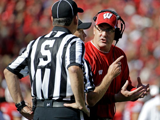 Wisconsin head coach Paul Chryst, right, argues a call