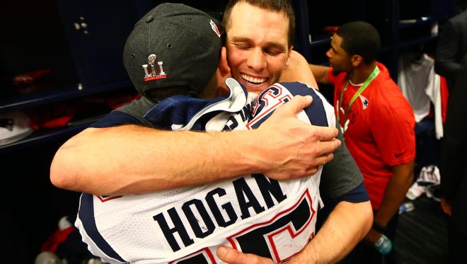 Tom Brady embraces Chris Hogan in the locker room after winning Super Bowl LI.