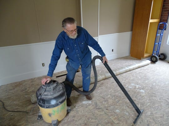 Charlie Harris, Sandusky County Habitat for the Humanity Project chairman, vacuums subflooring to prepare for new flooring at the Jackson Street house.