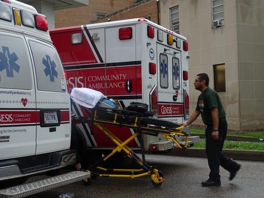 A worker unloads a gurney from a Community Ambulance
