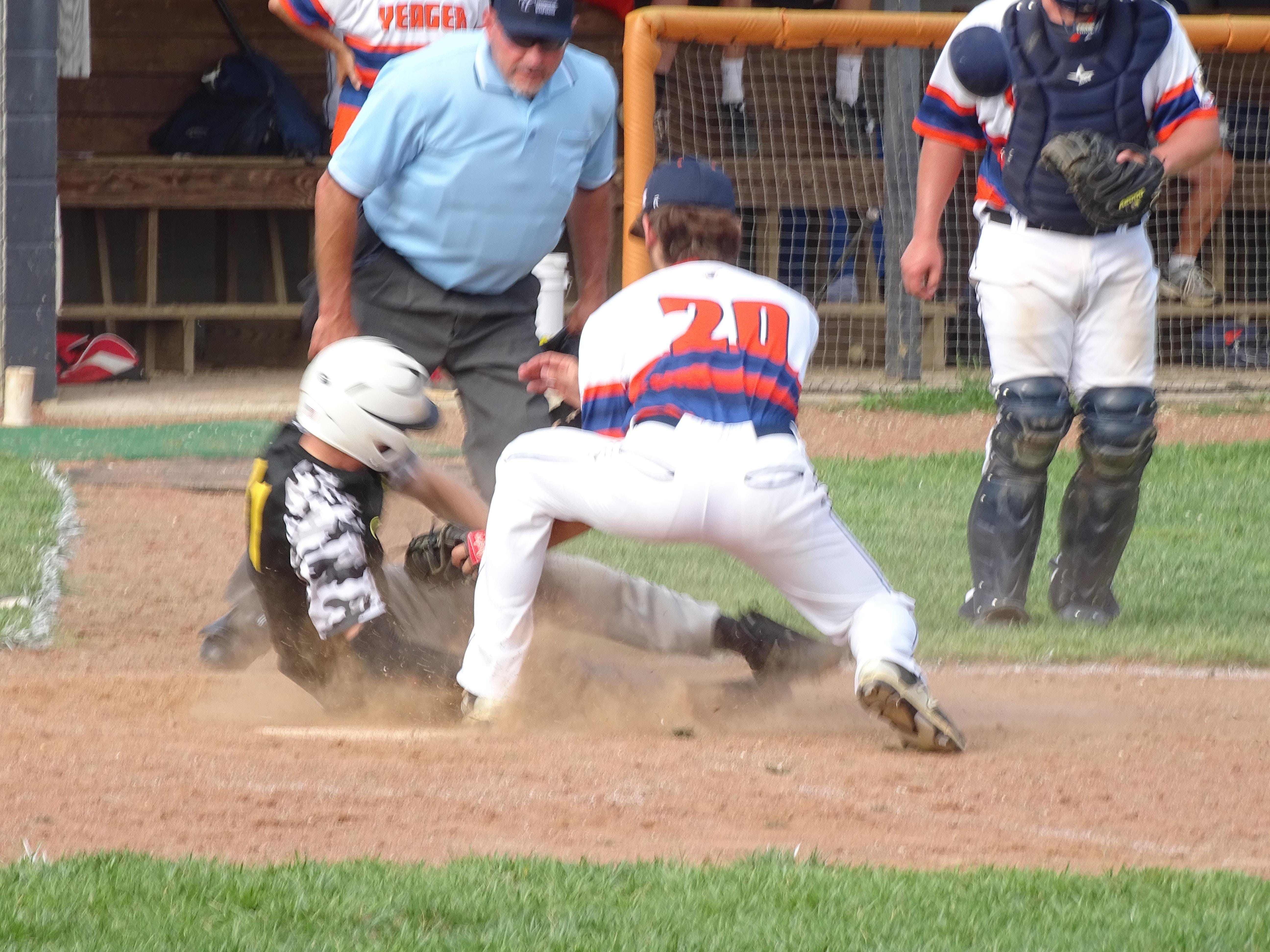 Waverly Post 142's Logan Kottebrook is tagged out sliding into home plate during the first inning of Thursday night's game against Cincinnati Yeager at Waverly High School. Post 142 fell to Yeager, 15-1.