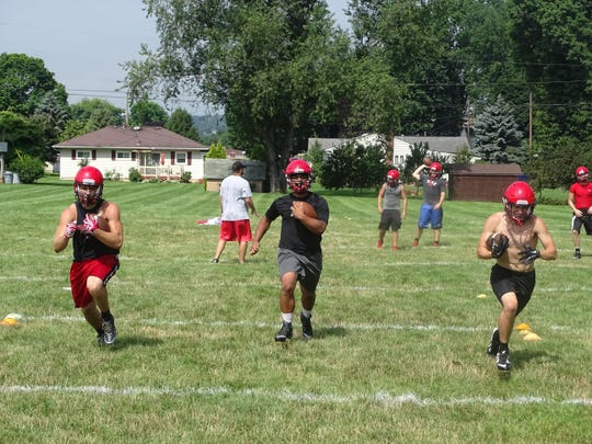 Three Coshocton runningbacks finish a handoff drill in Monday's practice.
