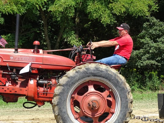 Jack Gibbs, of Fremont, tries to get a little more out of his 1950 Farmall tractor Sunday during the tractor pull competition at the S.C.R.A.P. festival. The festival is held annually at White Star Park in Gibsonburg.