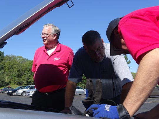 Donnis Slaughter, center, of Prince's Wrecker Service, assists AAA workers to check the engine of River View Junior Paige Douglas' Chevrolet Impala on Monday.