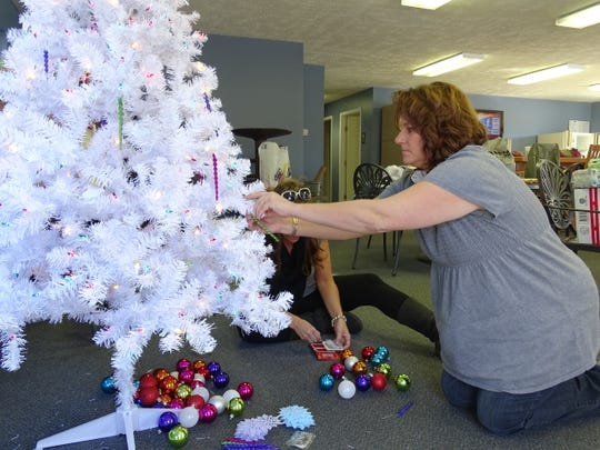 A Junior Civic League member prepares a Giving Tree