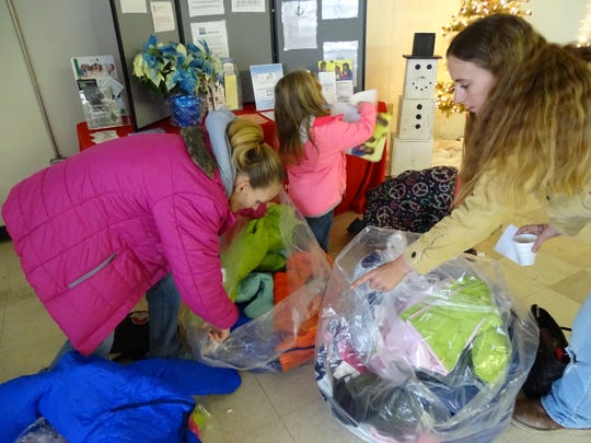 Families dig through piles of coat in search of the perfect size and color at the Ross County Community Action's coat giveaway.