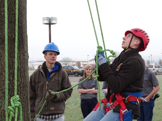 Career Center student Eric Maddux supervises Coshocton High School sophomore Jensen Green as he climbs a tree Thursday outside the Coshocton County Career Center. The joint vocational school's annual sophomore visitation day allows students from the three county school districts to see demonstrations and participate in hands-on activities.