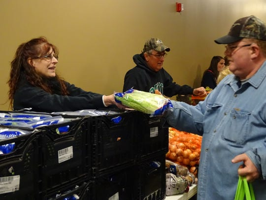 Heidi Stanley hands lettuce to Stan Murray during a food giveaway at Upper Assembly Room and Worship Center. The church, at 331 Main St., will give out items from the Mid-Ohio Foodbank at 5:30 p.m. every other Wednesday, with the next giveaway set for Jan. 21. Volunteers are needed to unload trucks and give out food.
