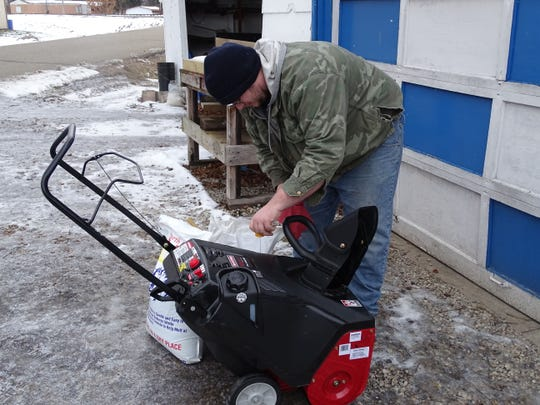 James Stull checks the oil on his snowblower. He cleans