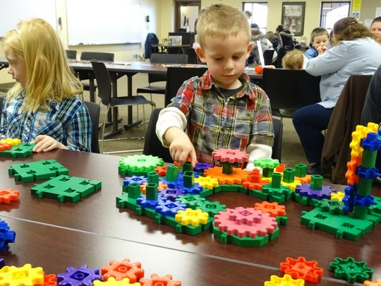 Three-year-old Josiah Moreland, center, works with gears Thursday at The Works Science Night at Central Ohio Technical College's Coshocton Campus.