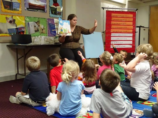 Alana Folk, youth services staff member at the Bellevue Public Library, reads to kids during story time Oct. 15, 2014.