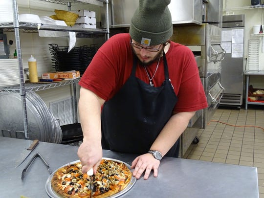 Drew Lochotzki slices up a Sicilian style pizza that